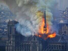 TOPSHOT - Smoke and flames rise during a fire at the landmark Notre-Dame Cathedral in central Paris on April 15, 2019, potentially involving renovation works being carried out at the site, the fire service said. - A major fire broke out at the landmark Notre-Dame Cathedral in central Paris sending flames and huge clouds of grey smoke billowing into the sky, the fire service said. The flames and smoke plumed from the spire and roof of the gothic cathedral, visited by millions of people a year, where renovations are currently underway. LEHTIKUVA / AFP  Hubert Hitier