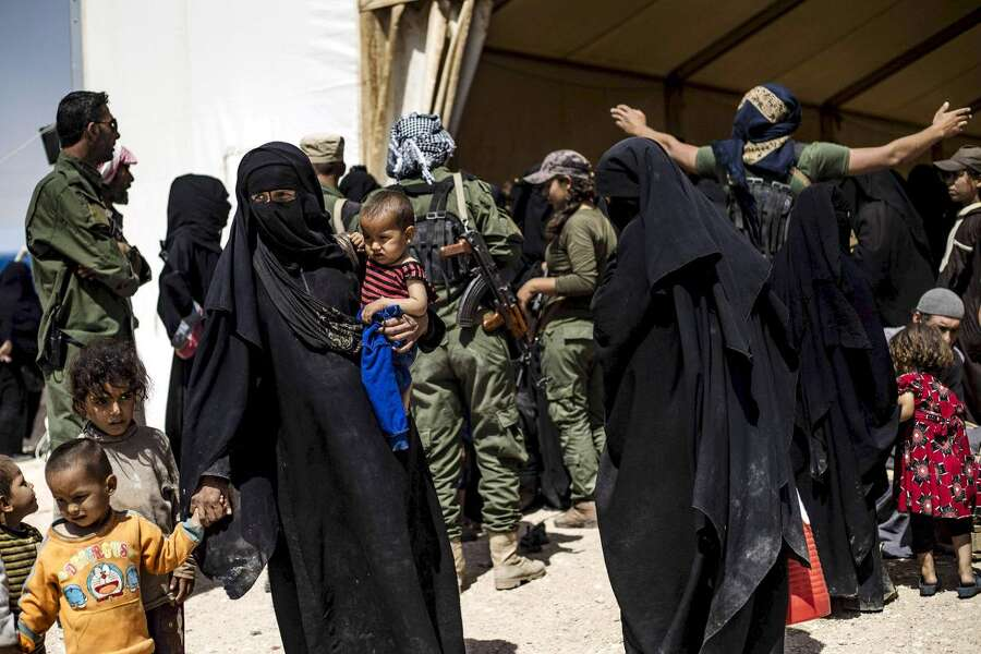 "LKS 20190705 Female fighter from the Syrian Democratic Forces (SDF) hand search displaced people before allowing them to board a bus waiting outside the Al-Hol camp in Al-Hasakeh governorate in northeastern Syria, on June 3, 2019, as Kurdish authorities started sending home 800 Syrian women and children who had been evacuated from the Islamic State group's ""caliphate"" earlier this year. - Al-Hol camp is bursting with Syrians, Iraqis and people from more than 40 other nations who fled successive US-backed assaults led by the Kurds against the last bastions of the Islamic State group's ""caliphate"". LEHTIKUVA / AFP Delil Souleiman"