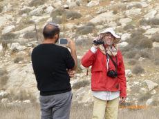Guy Butavia, mies punaisessa takissa, Rabbis for Human Rights ottaa kuvallisesti mittaa siirtokuntalaisrähinöitsijästä siirtokunta Otnielin ulkopuolella