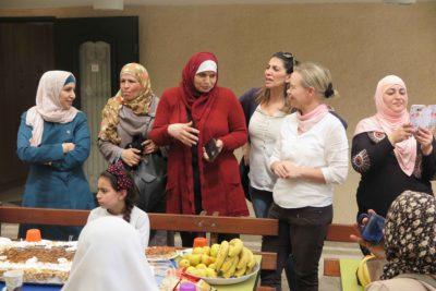 Huiveihin pukeutuneet naiset juttelevat iloisesti keskenään, mukana myös yksi vaalea suomalainen.