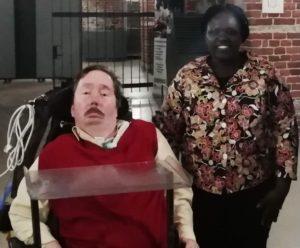 Sähköpyörätuolissa istuvan Jukka Sariolan vierellä seisoo Anjeline Okola